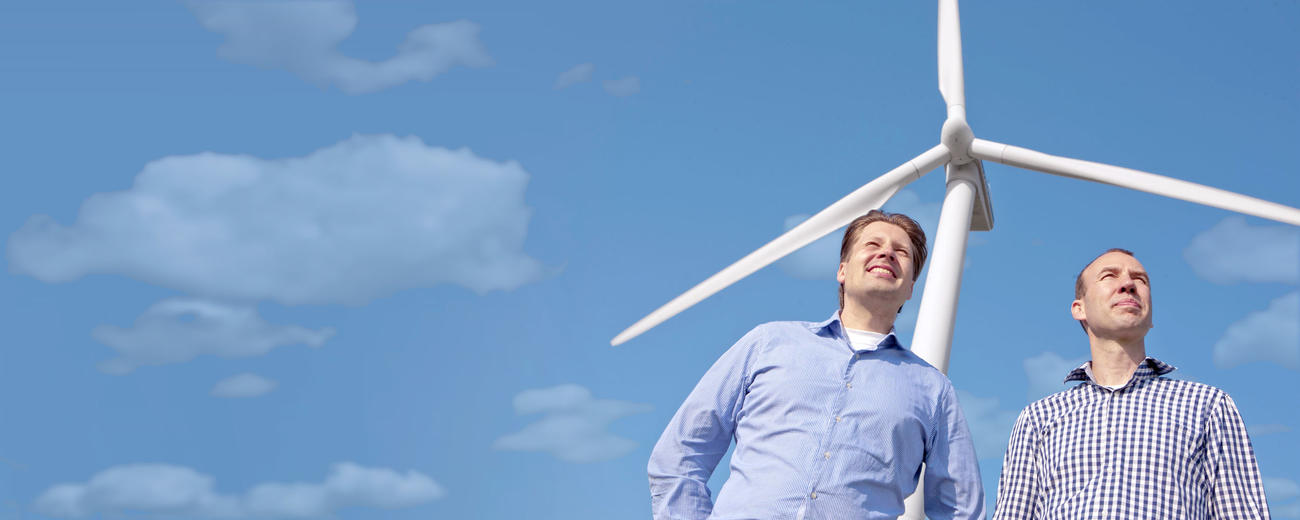 Founders in front of wind turbine