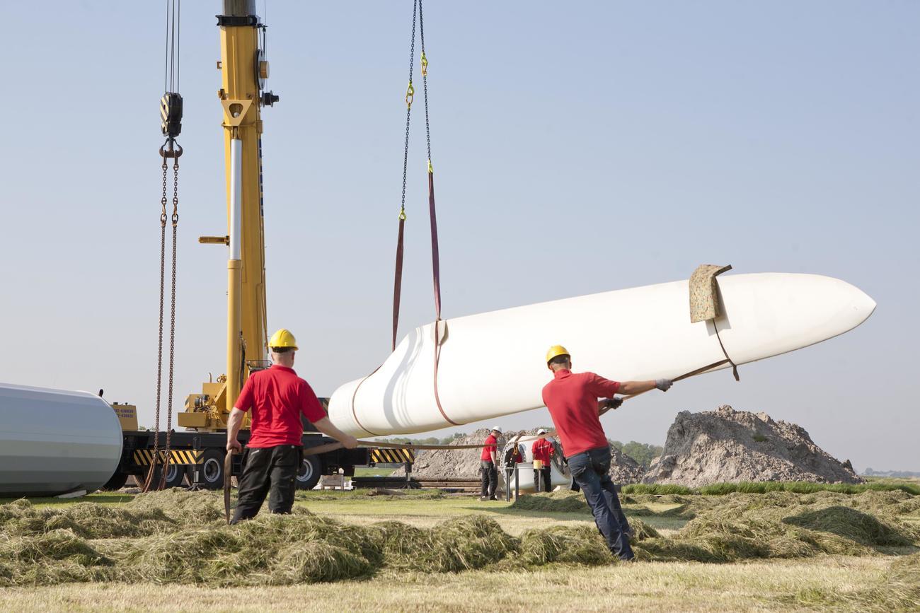 Workers assembling a wind turbine