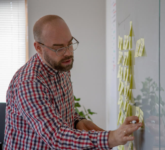 Man plakt tijdens brand spring post-its op een whiteboard